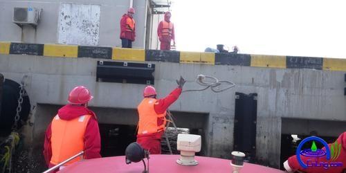 应急船员甩缆固定围油栏。